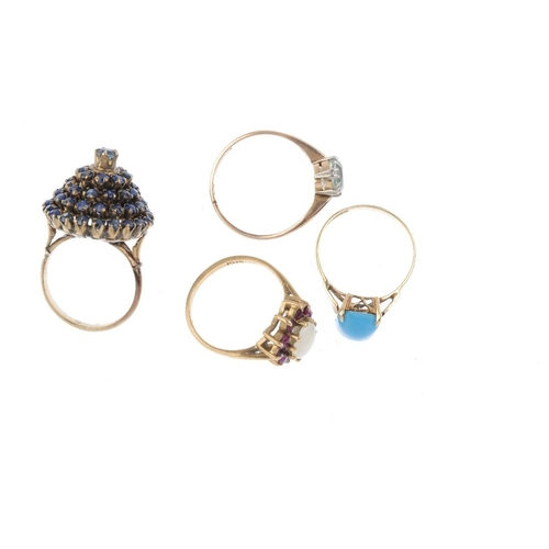 906 - Four gem-set dress rings. A 9ct gold opal and ruby cluster ring, a 9ct gold blue paste single-stone ...