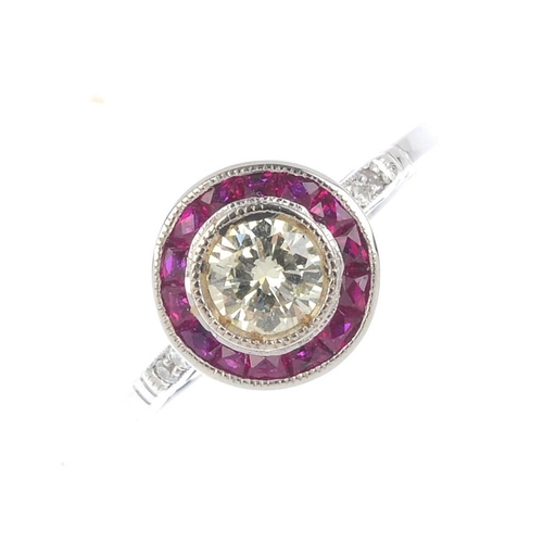 910 - A diamond and ruby cluster ring. The brilliant-cut diamond, with calibre-cut ruby surround and diamo...
