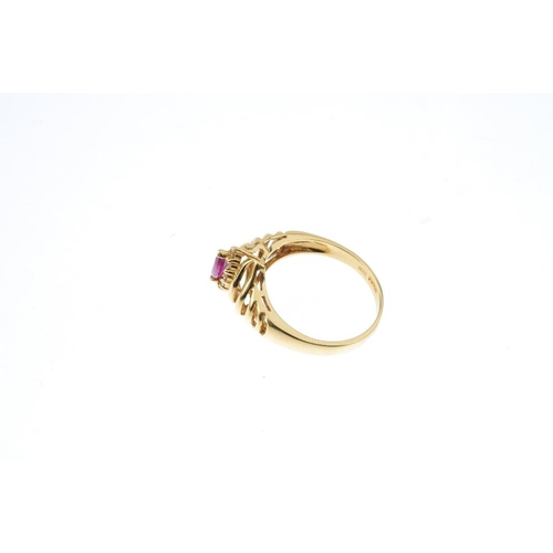 911 - An 18ct gold ruby and diamond cluster ring. The marquise-shape ruby, within a brilliant-cut diamond ...