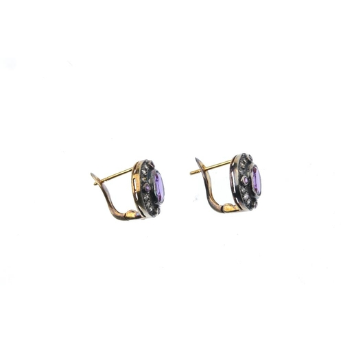 919 - A pair of amethyst and diamond earrings. Each designed as an oval-shape amethyst collet, within a ci...