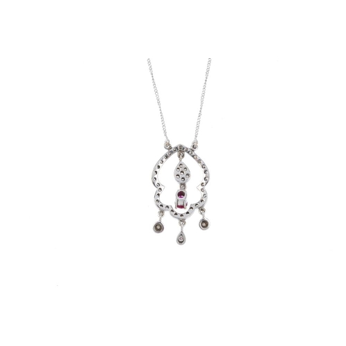 925 - A diamond and ruby pendant. Of openwork design, the oval-shape ruby and brilliant-cut diamond cluste...