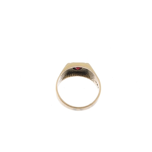 940 - A gentleman's 1970s 9ct gold garnet signet ring. The circular-shape garnet and square-shape surround...