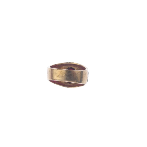 943 - A gentleman's 9ct gold paste single-stone ring. The oval red paste cabochon, with textured sides and...