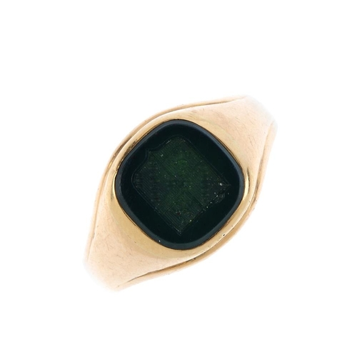 947 - A gentleman's bloodstone signet ring. The carved bloodstone depicting a coat-of-arms, with tapered s...