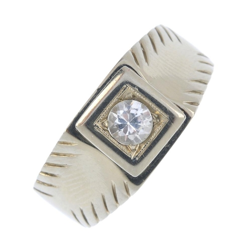 951 - A gentleman's paste ring. The circular-shape colourless paste, with engraved motif sides. Ring size ...