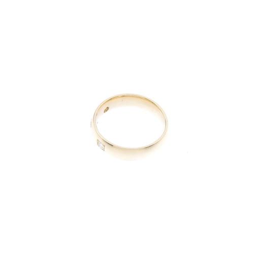 953 - A 9ct gold diamond band ring. Designed as three brilliant-cut diamonds inset into a plain band. Esti...