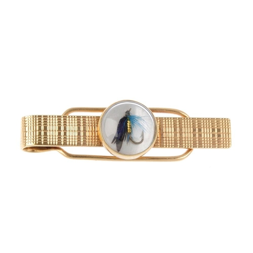 969 - A 1950s 9ct gold tie slide. The oval-shape mother-of-pearl panel, with overlaid feather fly-fishing ...