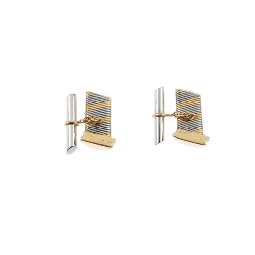 972 - A pair of cufflinks. Of bi-colour design, each designed as rectangular-shape panel, with grooved det...