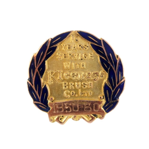 974 - A mid 20th century 9ct gold enamel long service button. The circular outline with blue enamel laurel...