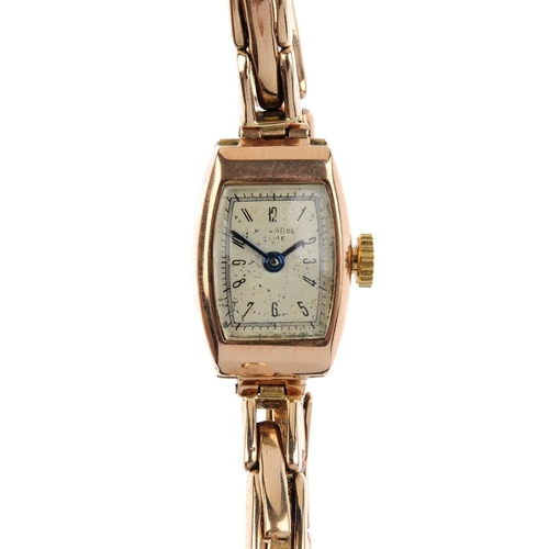 994 - A lady's 1940s 9ct gold manual-wind wristwatch. The tonneau-shape silver colour dial with Arabic num...