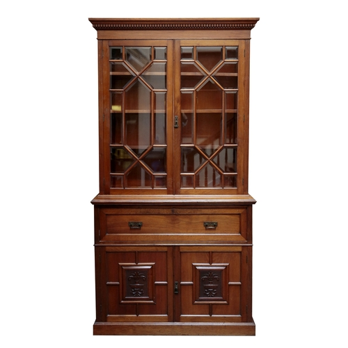 924A - A late Victorian carved walnut secretaire bookcase, the upper stage having a moulded dentil cornice ...