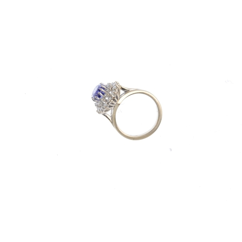12 - An 18ct gold tanzanite and diamond cluster ring. The oval-shape tanzanite, with brilliant-cut diamon...
