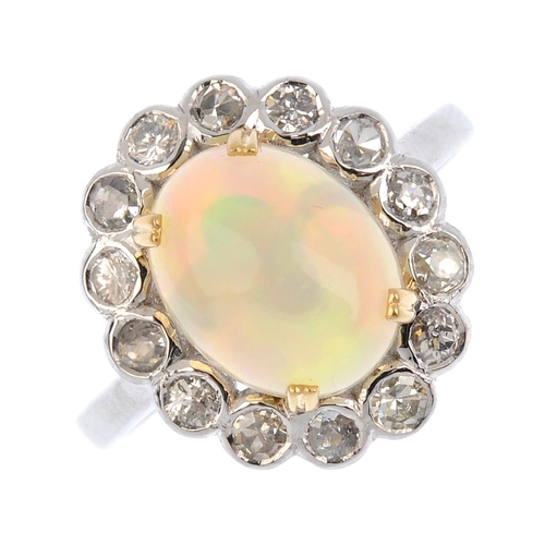 131 - An opal and diamond cluster ring. The oval opal cabochon, with vari-cut diamond collet surround. Est...