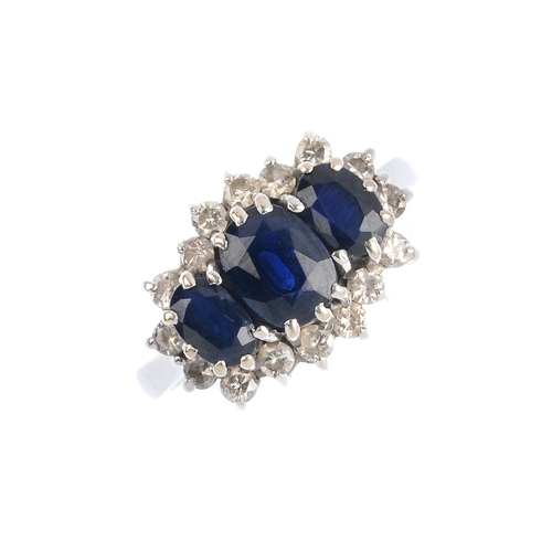 135 - A sapphire three-stone and diamond ring. The graduated oval-shape sapphire line, with brilliant-cut ...