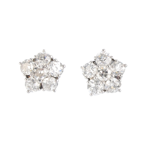 136 - A pair of diamond cluster earrings. Each designed as an old-cut diamond, with similarly-cut diamond ...