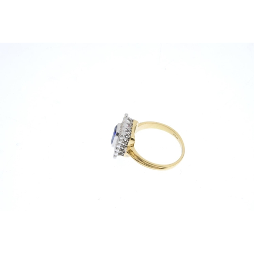 137 - An 18ct gold sapphire and diamond cluster ring. The rectangular-shape sapphire, with brilliant cut d...