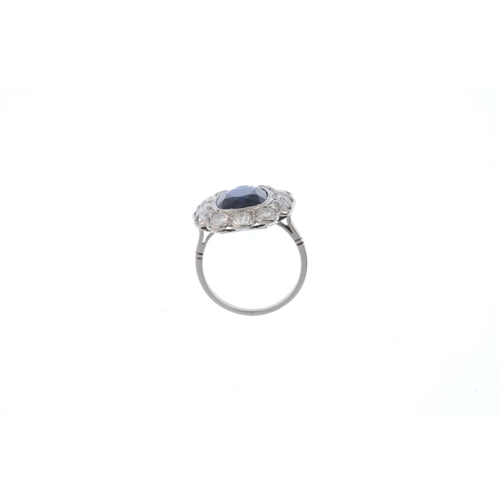 140 - A mid 20th century platinum sapphire and diamond cluster ring. The oval-shape sapphire, with vari-cu...