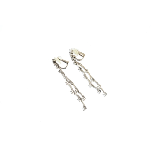 147 - A pair of diamond earrings. Each designed as two brilliant-cut diamond articulated lines, with bague...