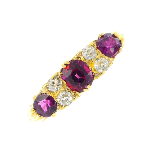 148 - A ruby three-stone and diamond ring. The cushion-shape ruby graduated line, with old-cut diamond lin...