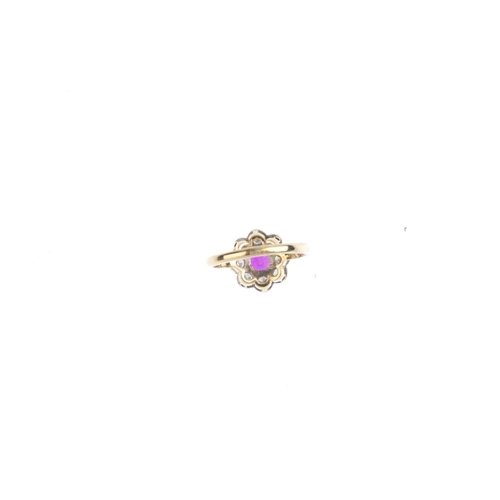 151 - An 18ct gold Thai ruby and diamond cluster ring. The circular-shape ruby, weighing 0.87ct, with bril...