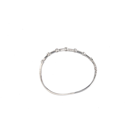 156 - A diamond bangle. The undulating bangle, with brilliant-cut diamond collet spaced line. Estimated to...