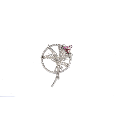 164 - An early 20th century platinum diamond and ruby floral brooch. The vari-cut diamond floral spray, wi...