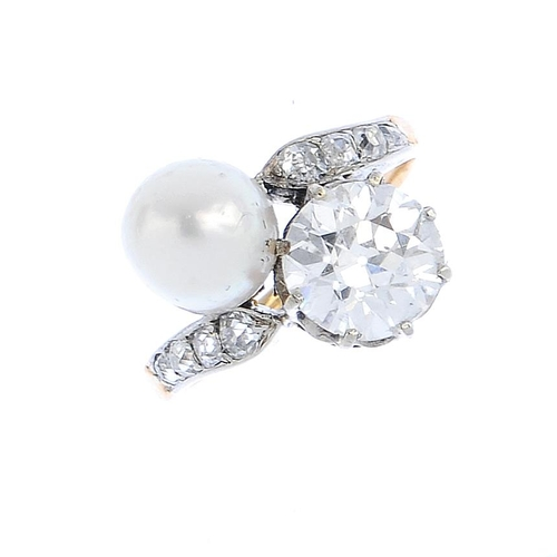 172 - A natural pearl and diamond crossover ring. The pearl and circular-cut diamond, with graduated old-c...