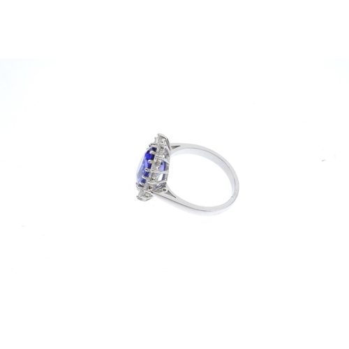 180 - An 18ct gold tanzanite and diamond cluster ring. The oval-shape tanzanite, with brilliant-cut diamon...