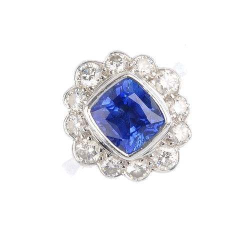 182 - An 18ct gold sapphire and diamond cluster ring. The cushion-shape sapphire, with brilliant-cut diamo...