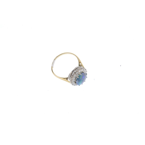 183 - A black opal and diamond cluster ring. The oval opal cabochon, with brilliant-cut diamond surround. ...