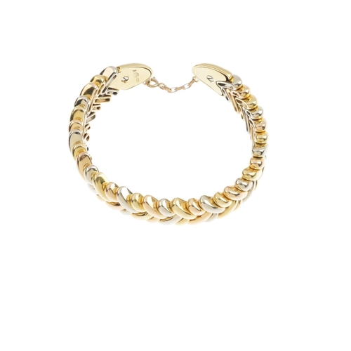 188 - GEORG JENSEN - a bangle. The open cuff, with tri-colour, woven motif and tapered terminals. Maker's ...