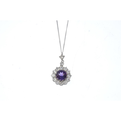 198 - A diamond and amethyst cluster pendant. The circular-shape amethyst, within a circular-cut diamond s...