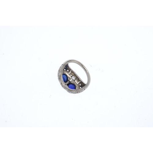 209 - A sapphire and diamond dress ring. The twin circular sapphire cabochons, with vari-cut diamond, pier...
