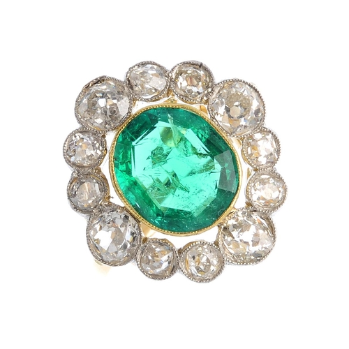 216 - A Colombian emerald and diamond cluster ring. The oval-shape emerald, with old-cut diamond surround....