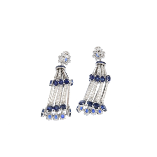 223 - MOUAWAD - a pair of sapphire and diamond earrings. Each designed as an oval-shape sapphire and brill...
