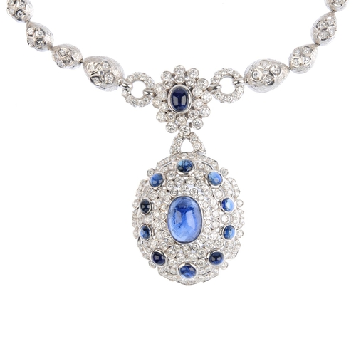 226 - A sapphire and diamond necklace. The oval sapphire cabochon with brilliant-cut diamond and circular ...