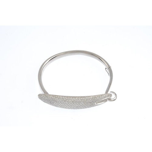 231 - A diamond hinged bangle. The pave-set diamond oval panel, with hook accent, to the hinged bangle. Es...