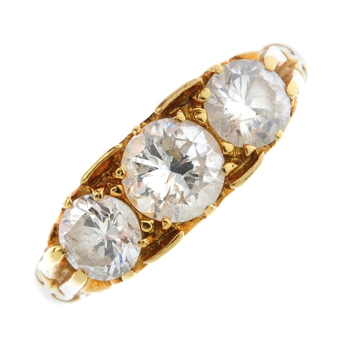 243 - An 18ct gold diamond three-stone ring. The graduated brilliant-cut diamond line, with scrolling gall...