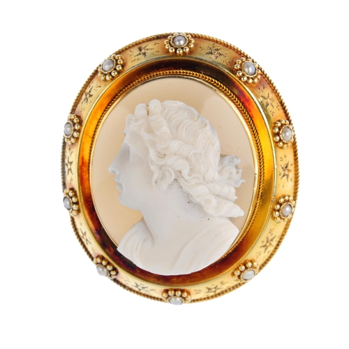 251 - A mid Victorian gold cameo brooch. Of oval outline, the agate cameo, carved to depict a lady in prof...