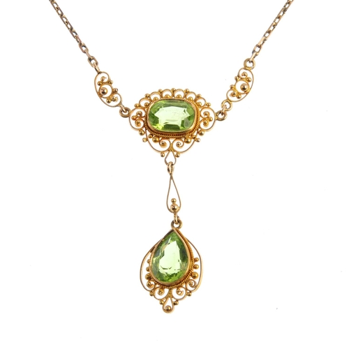 26 - An early 20th century gold peridot necklace. The pear-shape peridot suspended from a cushion-shape p...