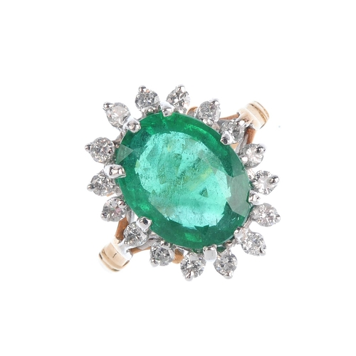 264 - An emerald and diamond cluster ring. The oval-shape emerald, with brilliant-cut diamond surround and...