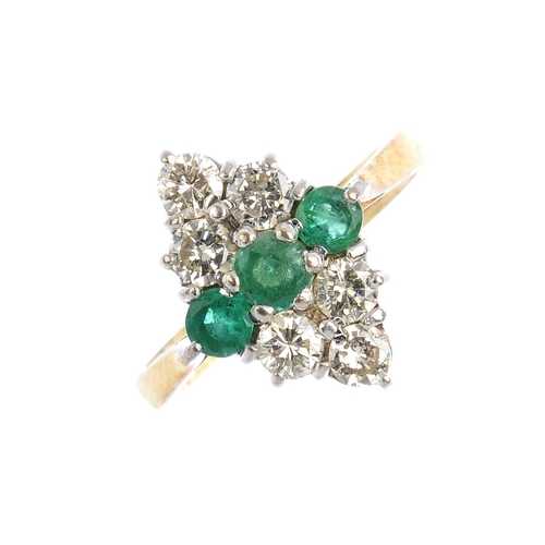 267 - An emerald and diamond cluster ring. The circular-shape emerald line, with brilliant-cut diamond tre...