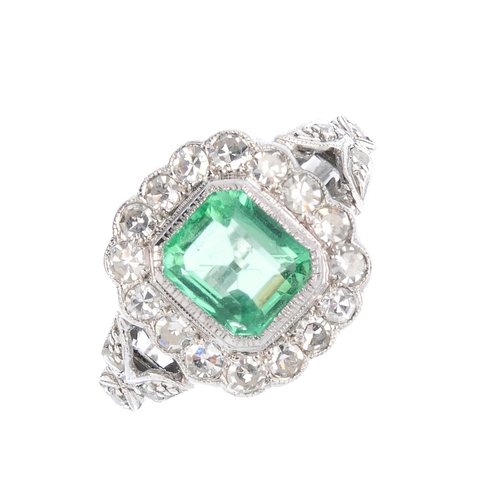 268 - A Colombian emerald and diamond cluster ring. The rectangular-shape emerald, weighing 1.22cts, with ...