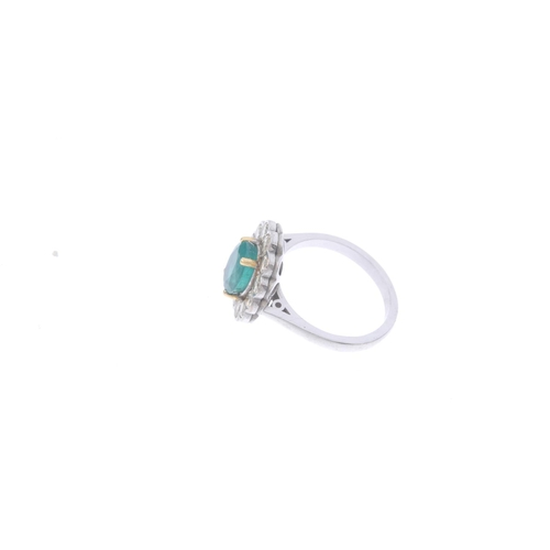 269 - An 18ct gold emerald and diamond cluster ring. The oval-shape emerald, with brilliant-cut diamond sc...