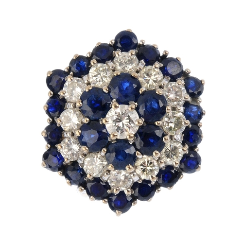 274 - A sapphire and diamond cluster ring. Of hexagonal outline, the brilliant-cut diamond, within an alte...
