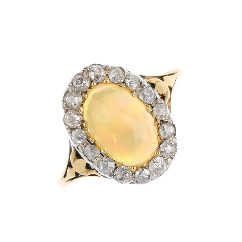 281 - An opal and diamond cluster ring. The oval opal cabochon, with old-cut diamond surround. Opal weight...