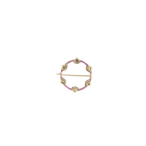 29 - An early 20th century gold diamond and gem-set wreath brooch. The calibre-cut ruby circle, with rose...