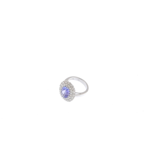 292 - A tanzanite and diamond cluster ring. The oval-shape tanzanite, with brilliant-cut diamond double su...