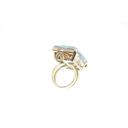 297 - A 14ct gold aquamarine and diamond cocktail ring. The rectangular-shape aquamarine with single-cut d...