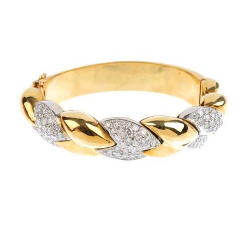 300 - A diamond hinged bangle. Of bi-colour design, the pave-set diamond and polished interwoven lines, to...